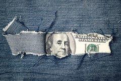 一百元钞票通过被撕毁的蓝色牛仔裤纹理 库存图片