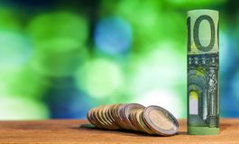 一百欧元在绿色滚动了票据钞票,与欧洲硬币 免版税库存照片