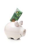 一百欧元钞票和两欧元硬币插入物到白色瓷猪里 免版税库存图片