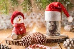 一百美元与雪人的钞票在一个红色盖帽 免版税库存照片