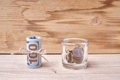 一百美元和分在一张木桌上 库存照片