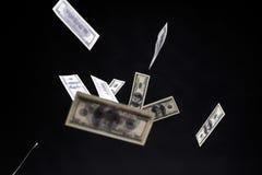 一百美元钞票在黑背景的被隔绝的飞行 库存照片