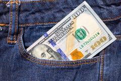 一百美国在蓝色牛仔裤的口袋的美金 免版税图库摄影