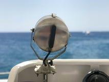 一盏大灯,聚光灯,一盏探照灯在小船,以一个美好的热带风景为背景的一艘船的中心 免版税库存图片