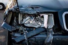 一盏残破的前灯的细节在一辆深蓝汽车的 图库摄影