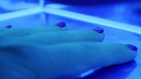 一盏紫外被带领的灯的特写镜头用在修理胶凝体指甲油里面的一只女性手在美容院 股票录像