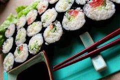 一盒寿司卷服务用棍子和酱油 免版税库存照片
