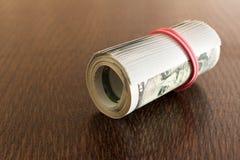 一盒扭转的100美金 在一张木表 关闭 免版税库存图片