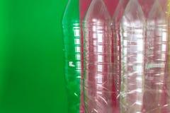 一盒空和可再循环的塑料水瓶,在色的充满活力的绿色和葡萄酒红背景 再用,Eco 免版税库存图片
