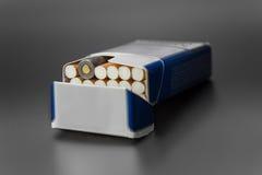 一盒香烟与一实弹射击的在组装 免版税库存照片