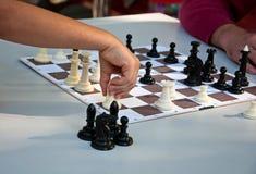 一盘象棋 下棋的孩子和人 免版税库存照片