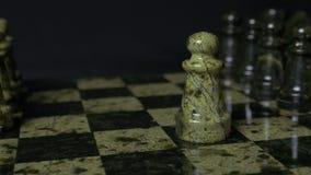 一盘象棋 白色典当击败黑典当 选择聚焦 棋典当被击败的典当 棋子细节在黑色的 免版税库存图片