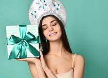 一相当微笑的gir的画象在拿着礼物盒的传统俄国盖帽kokoshnik的 免版税库存图片