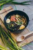 一碗与三文鱼片断的新鲜的大酱汤在竹背景的 免版税库存图片