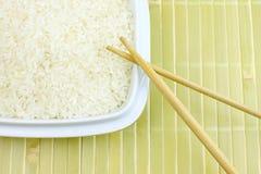 一碗与筷子的未加工的白米在竹背景 库存照片