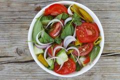 一碗从蕃茄、菠菜和各种各样的新鲜蔬菜的莴苣 免版税库存照片