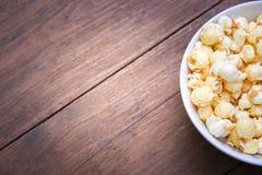 一碗在一张木桌上的玉米花 图库摄影