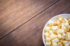 一碗在一张木桌上的玉米花 免版税库存图片