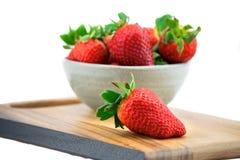 一碗在木板的成熟草莓 库存照片