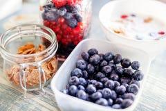 一碗在桌、麦子剥落和homem上的新鲜的蓝莓 免版税库存照片