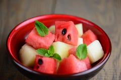 一碗混杂的热带水果沙拉:西瓜和瓜在一张木桌上 夏天水多的维生素沙拉  库存图片
