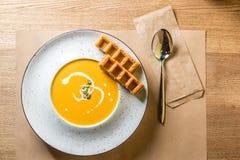 一碗辣南瓜汤用比利时华夫饼干 传统秋天食物 从家庭厨房或家庭咖啡馆的照片 免版税库存照片
