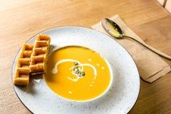 一碗辣南瓜汤用比利时华夫饼干 传统秋天食物 从家庭厨房或家庭咖啡馆的照片 免版税库存图片