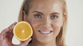 一种健康生活方式的伟大的食物 拿着桔子的片断在她的眼睛前面的美丽的年轻赤裸上身的白肤金发的妇女 股票视频