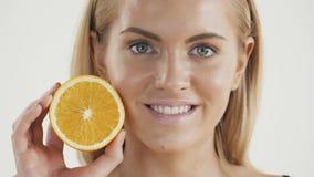 一种健康生活方式的伟大的食物 拿着桔子的片断在她的眼睛前面的美丽的年轻赤裸上身的白肤金发的妇女 股票录像