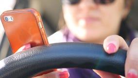 一种好心情的一个女孩在汽车的轮子,紧贴到轮子,敲对此与她的手指,舞蹈, 免版税库存图片