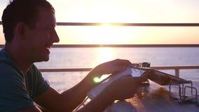 一种好心情的一个年轻人,在咖啡馆坐与日落的海滩,纸卷通过菜单,要做出选择 影视素材