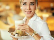 一种好心情的微笑的妇女与坐在咖啡馆的咖啡 免版税库存照片