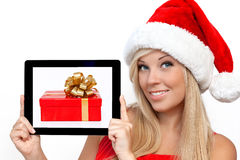 一种红色圣诞节帽子藏品片剂的女孩 免版税库存照片