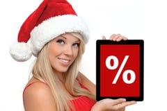 一种红色圣诞节帽子藏品片剂的女孩 库存图片