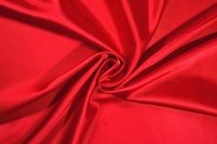 从一种红色缎织品的背景 免版税库存图片