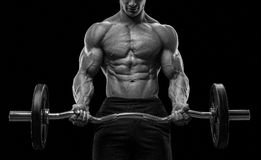 一种肌肉人锻炼的特写镜头画象与杠铃的在健身房 免版税库存图片