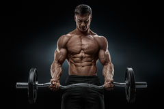 一种肌肉人锻炼的特写镜头画象与杠铃的在健身房