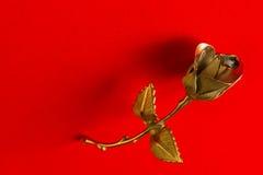 一种金属在假日问候的红色背景上升了 库存照片