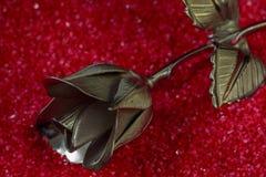 一种金属在假日问候的红色背景上升了 免版税图库摄影