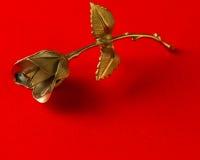 一种金属在假日问候的红色背景上升了 免版税库存图片