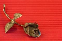 一种金属在假日问候的红色背景上升了 库存图片