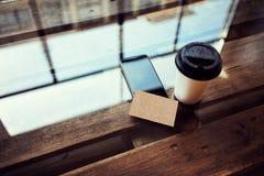 一空白的牛皮纸名片大模型木头表 拿走咖啡杯Coworking咖啡馆 现代电话工作办公室 库存图片