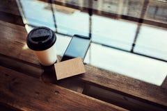 一空白的牛皮纸名片大模型木头表 拿走咖啡杯Coworking地方 现代电话工作办公室 免版税库存图片