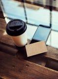 一空白的牛皮纸名片大模型木头表 拿走咖啡杯Coworking地方 现代电话工作办公室 库存照片
