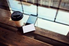 一空白的白皮书名片大模型木头表 拿走咖啡杯Coworking咖啡馆 现代电话工作办公室 免版税库存图片