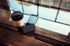 一空白的黑名片大模型木头表 拿走咖啡杯Coworking咖啡馆地方 现代电话工作办公室 免版税库存图片