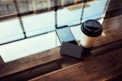 一空白的黑名片大模型木头表 拿走咖啡杯Coworking演播室地方 现代电话工作办公室 库存照片