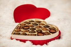 一箱在一条白色毛皮毯子的巧克力 免版税库存照片