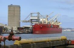 一箱红色货船装货货物在新堡靠码头 图库摄影