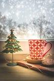 一红色咖啡杯和圣诞装饰的看法在一个窗口有多雪的背景 免版税库存照片